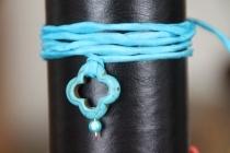 """Rehaussée par un ruban de soie turquoise, ton de l'été et des peux bronzées, cette superbe croix évidée a la majesté de la pierre et l'éclat de l'azur. Elle porte une mini perle bleue dite """"miracle"""", parfaitement coordonnée à la soie. Comme tous nos liens, c'est un bijou multiple en un : à porter en collier long pour un look casual chic, ras-du-cou pour une allure plus sport ou en bracelet plusieurs rangs pour l'été."""