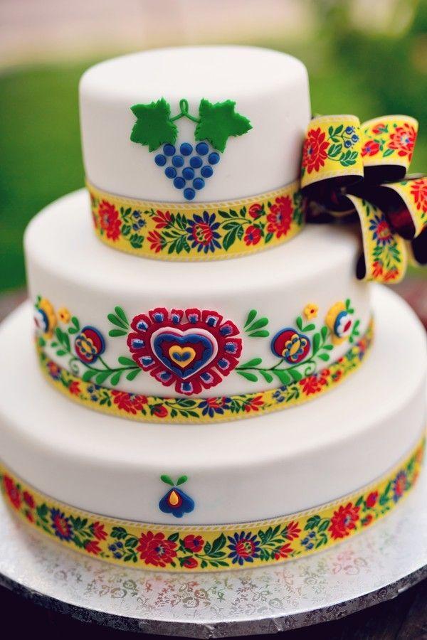 Třípatrový svatební dort potažený bílým fondánem a ozdobený plastickými folkovými ornamenty.