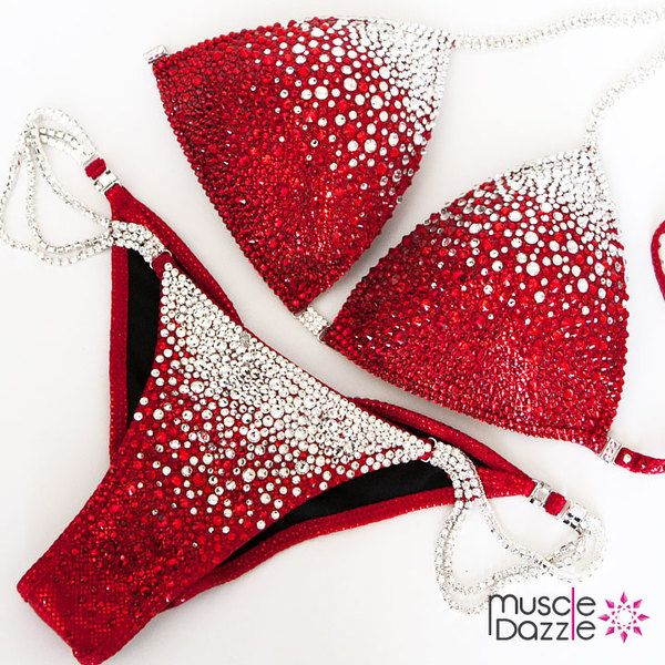 A red competition bikini decorated with white , light siam and siam crystals.