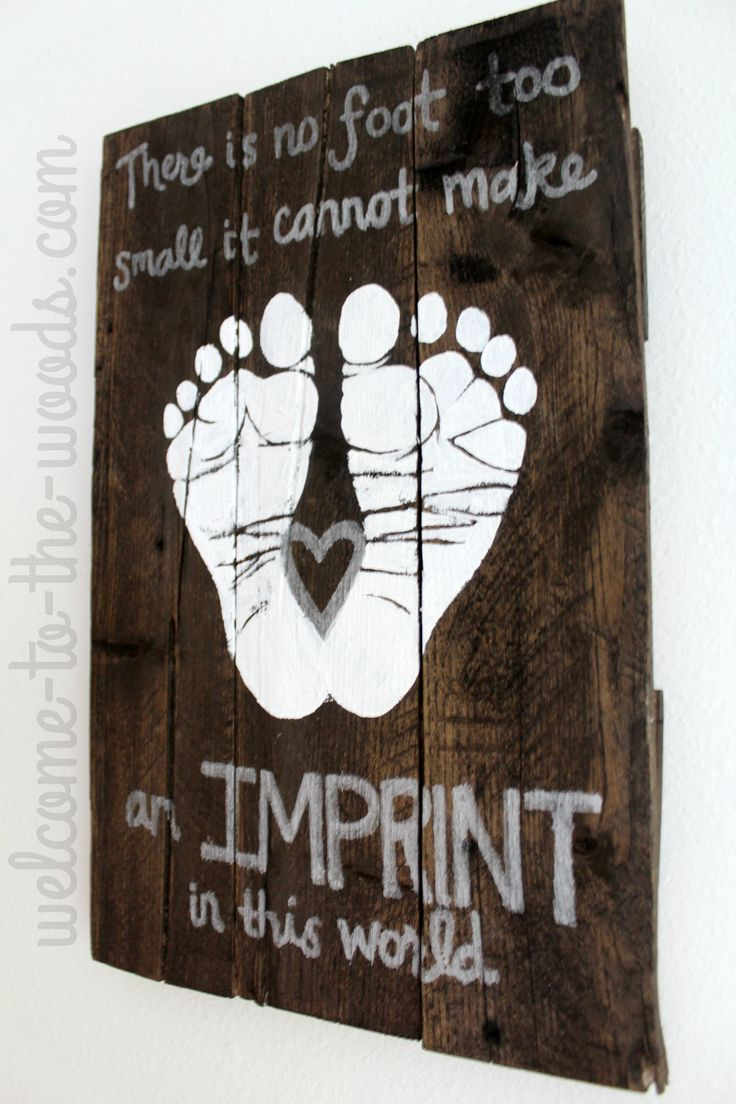 Stained pallet wood sign with baby footprints as nursery decor