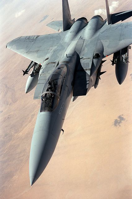 A U.S. Air Force F-15 Eagle aircraft flies a patrol over the desert during the cease-fire between coalition and Iraqi forces following Operation Desert Storm. The aircraft is carrying four AIM-9 Sidewinder missiles on its wing pylons and an AIM-7 Sparrow missile beneath its fuselage.