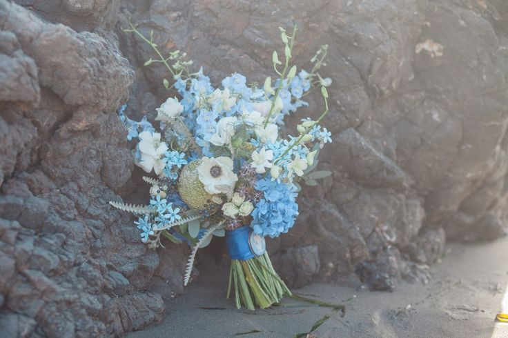 Seaside Whimsy Wedding: Bridal Bouquet. The florals combined feminine blooms with textural and architectural elements reminiscent of the sea. The bridal bouquet features a king protea, anemone, orchids, delphinium, tweedia, hydrangea, eucalyptus seeds, and private berry. It's is finish with silk ribbon and an antique brooch.