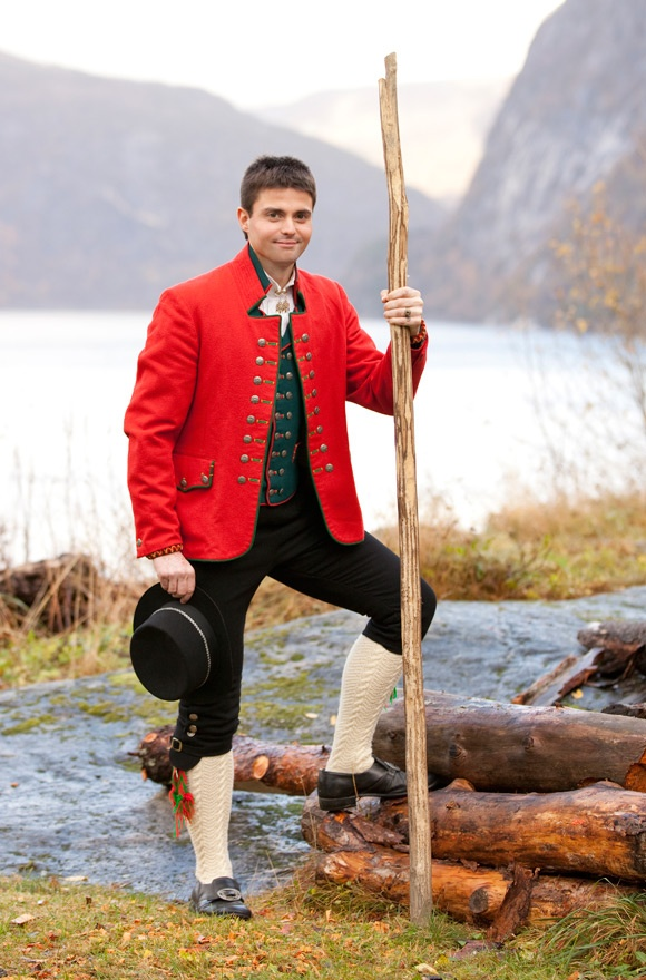 A dark green waistcoat can also be worn with the red jacket. At the wrists he is wearing embroideredwristlets of coarse woolen cloth with napped edgings. The hat is trimmed with silk ribbon and a silver lace. The collar on his shirt is closed with asilverbutton with hanging leaves. Hardanger