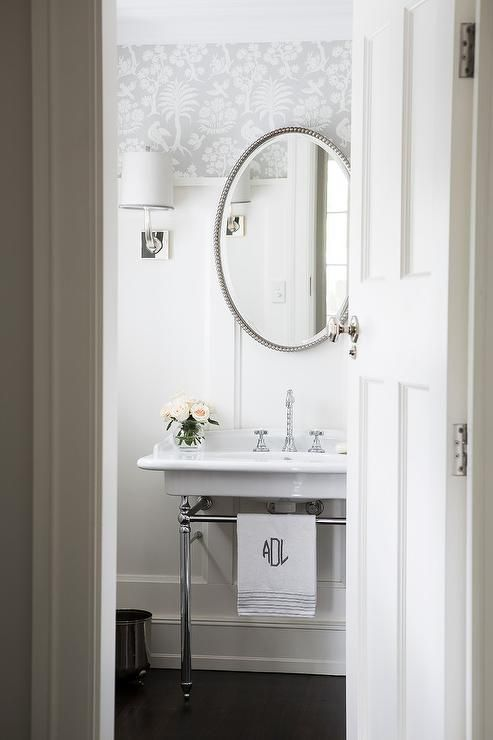 White and silver transitional powder room boasts a nickel and marble 2 leg washstand placed on dark wood floors and fitted with a polished nickel cross handle faucet positioned beneath an oval beaded mirror mounted on a white board and batten trim accented by silver wallpaper illuminated by a nickel sconce adorning a white shade.