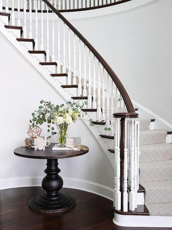 Elegant foyer features a curved staircase a stained handrail and white spindles as well as a gray diamond pattern stair runner lining the steps. Foyer boasts a distressed black round foyer table lining the curved staircase wall.