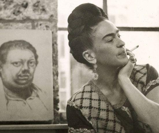 « Pensavano che anche io fossi una surrealista, ma non lo sono mai stata. Ho sempre dipinto la mia realtà, non i miei sogni. » Questo dichiara Frida Kahlo in un'intervista del 1953. La pittrice messicana è qui fotografata con sullo sfondo il ritratto del marito, l'artista Diego Rivera. La loro appassionata e tormentata storia d'amore viene raaccontata da Frida nel suo diario. Ebbe numerosi amanti, di ambo i sessi, fra i quali spicca il nome di Lev  Trotsky.