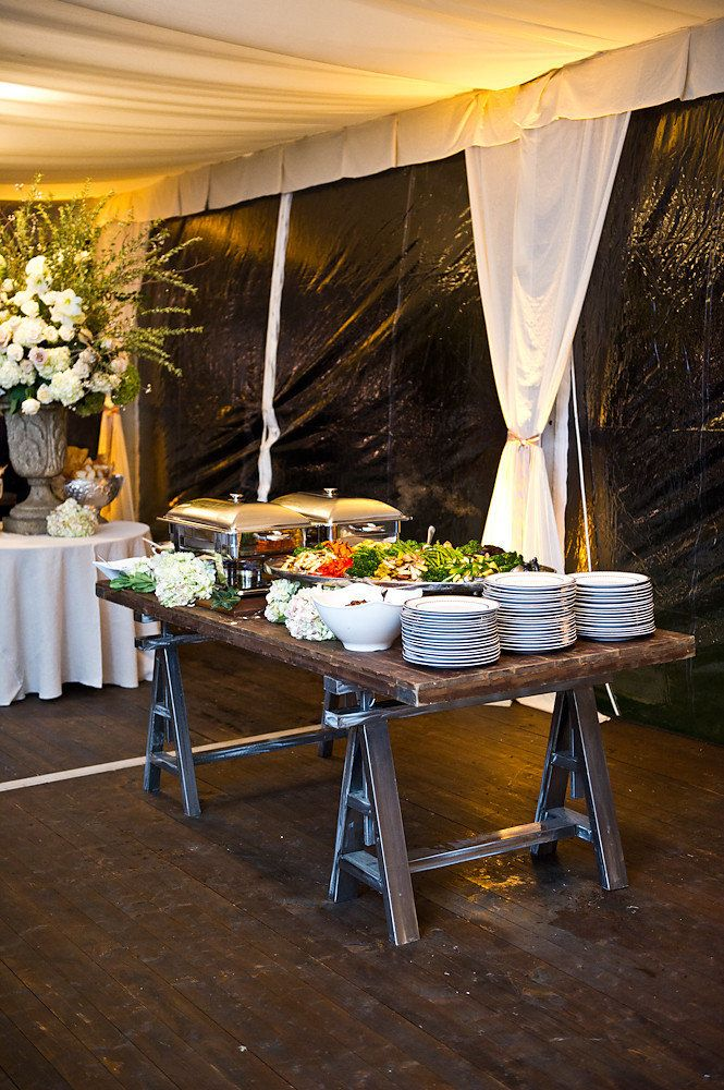 A cleanly draped linen table looks great when combined with the rustic look of a saw horse and an old door table. Creativity abounds and makes your wedding YOU!