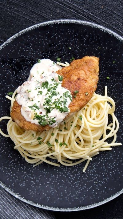 This twist on an Italian classic features perfectly browned fried chicken over a bed of pasta covered in a creamy, cheesy carbonara sauce.