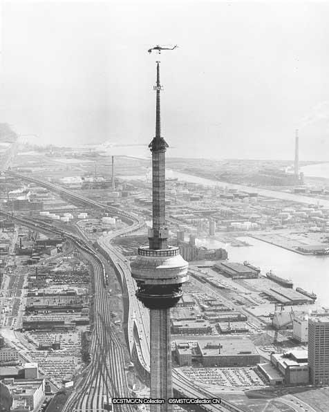 A helicopter installs a section of antenna mast of the CN Tower in Toronto, 1975.