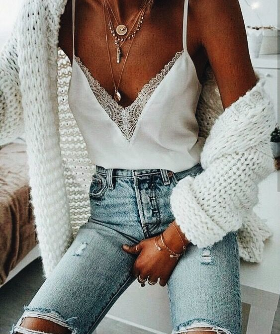 stunning spring outfit with distressed jeans, white chunky knit cardigan, lace insert camisole, and layered necklaces