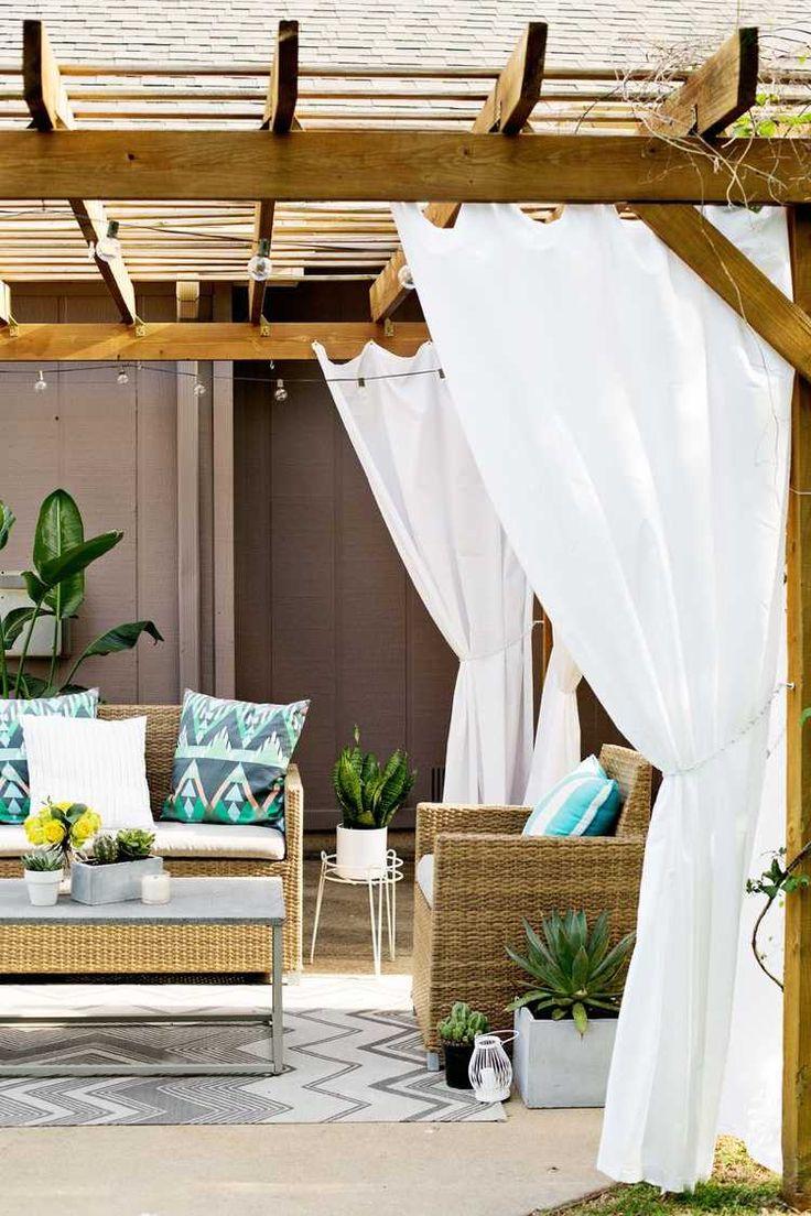 pergola en bois décorée de rideaux blancs, tapis extérieur et coussins à motifs bariolés