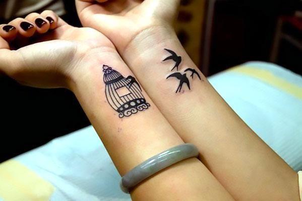Black bird cage and birds tattoo idea of wrist.