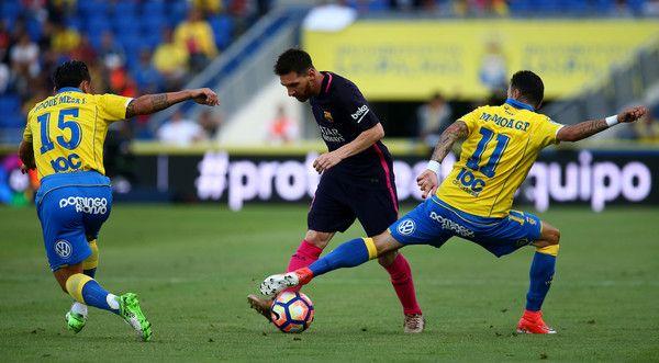 Lionel Messi of Barcelona looks to get past Las Palmas Roque Mesa (L) and Momo (R) during the La Liga match between UD Las Palmas and Barcelona at Estadio de Gran Canaria on May 14, 2017 in Las Palmas, Spain.