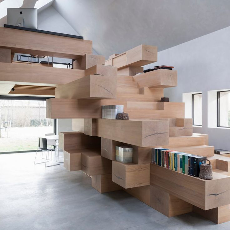 Timber beams are stacked to form this Jenga-like staircase, which has cupboards and shelves integrated into the overhangs of various steps. Studio Farris Architects added a platform on top of the structure to host an office with two workstations.