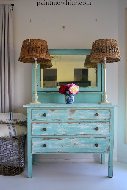 Perfectly beachy turquoise dresser and wicker lampshades with Pacific written on them.