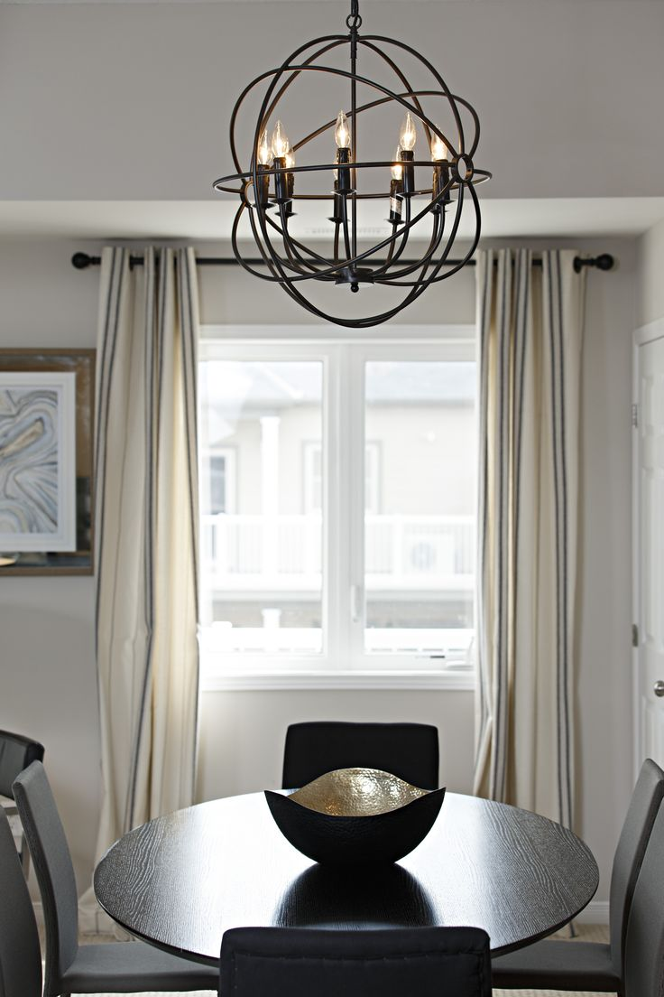 Modern Industrial Pendant Light Above Dark Hardwood Table In Family Home Dining Area