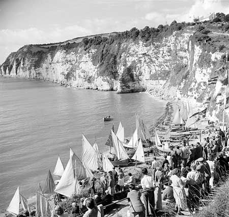 """Spectators gathered by the shore for the annual regatta at Beer in Devon, showing the Beer fishing luggers on the shore with their sails set.  Photographer:	Hallam Ashley, August 1950"""