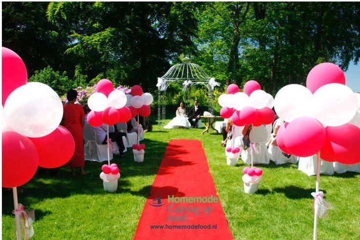Trouwen in de tuin van Kasteel Keukenhof. Ballon boompjes langs de rode loper van de ceremonie opstelling. Kleurthema van de dag; rood & wit. Homemade Catering op Maat denkt graag met u mee.