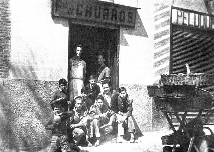 Churrería situada en el número 2 de la calle de Lago Constanza (antigua Castaño y Alba). Era propiedad de Luis Pérez Peña, que la abría todos los días a las cuatro de la mañana. Se hacían churros, porras y buñuelos, los cuales eran atados con €œjuncos€ que se encontraban en las orillas de los ríos). En la foto destaca la pila de cestas de mimbre empleadas por los repartidores, junto a la chiquillería del barrio. Foto de 1957. Foto de Fernando Pérez Peña.