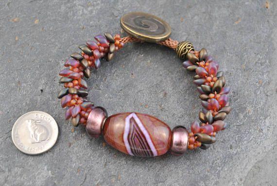 Agate & Lampwork Dragon Scales Kumihimo Artisan Bracelet #bracelet #kumihimo #kumihimobracelet #artisan #artisanbracelet #oneofakind #handmade #knotted #woven #handwoven #handknotted #boho #bohemian #druzy #druzyagate #agate #lampwork #foil #lampworkfoil #foilbeads #miyuki #seedbeads #magatama #japanese #iridescent #pink #bronze #plum #unique #flexible #lightweight #focalbead #striped #stripedfocalbead