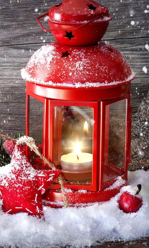 rote Laterne mit brennender Kerze im Schnee
