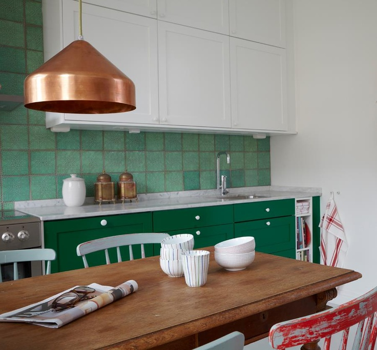 green tile kitchen with wood table and copper pendant.