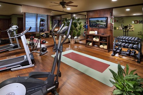 Home gyms don't have to be ugly. This room proves it with sleek laminate flooring, wood paneling and a sage-green accent wall.