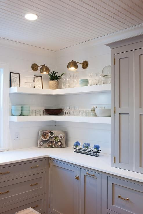 White and gray kitchen features light gray cabinets painted Farrow & Ball Dove Tale paired with white quartz countertops and a shiplap backsplash lined with stacked wraparound shelves painted Farrow & Ball All White.