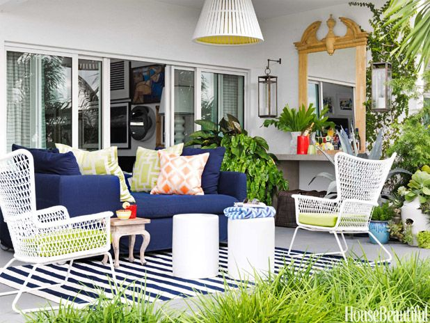 """A Lee Industries Nandina daybed upholstered in Solo outdoor fabric accommodates two in """"the nap zone."""" Pillow fabrics from Clarence House. The Dash & Albert Trimaran rug lends a breezy, beachy note. A Federal-style mirror, flanked by Riado lanterns, hangs above a Currey & Company console that serves as a bar. White tables by Emissary. Landscape design, Antonio Parrotta."""