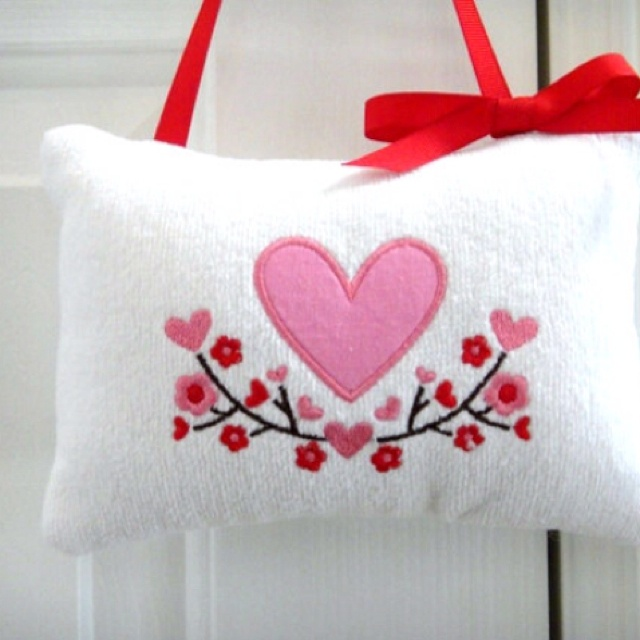 Repurposed from a white terry cloth fingertip towel, embroidered with a pink heart in the center surrounded by red and pink hearts and flowers. Finished with a red grosgrain ribbon for hanger and bow. etsy.com