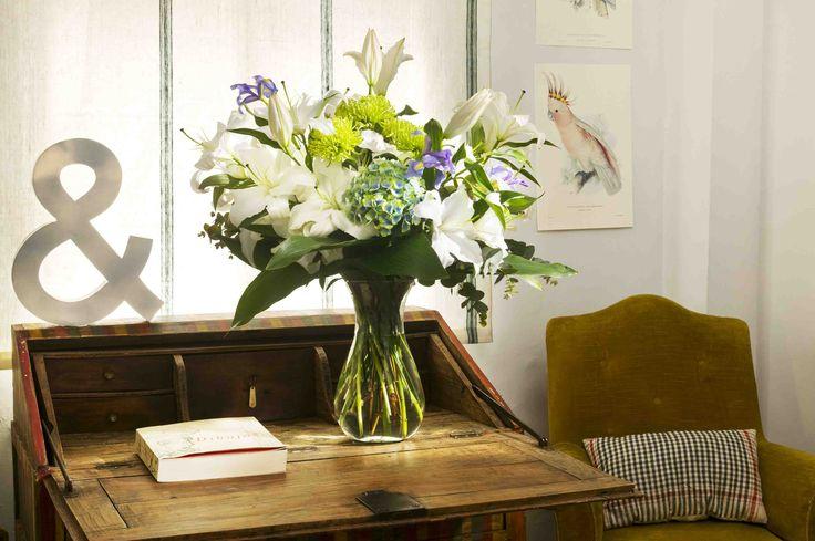 A lilium, iris, and hydrangea flower arrangement at a mezzanine | Un arreglo de flores de lilium, iris, y hortensias en una entre planta