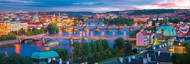 """Praque Czech Republic Panorama 1000-Piece Puzzle.  A beautiful view of Prague with the centerpiece of the Vltava River winding through the city! The various architectural styles are ever intriguing. Finished Puzzle Size: 13"""" x 38""""."""