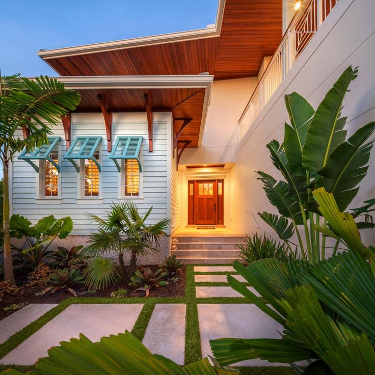 Large concrete slabs carve out a walkway to this stunning Florida home. Exterior design elements like rich wood soffits and decorative wood brackets pair with tropical landscaping to give the home an island-inspired look.