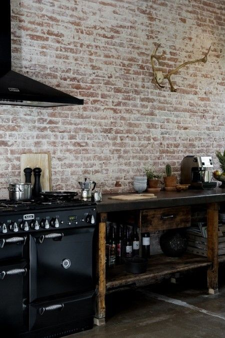 black kitchen w/ exposed brick