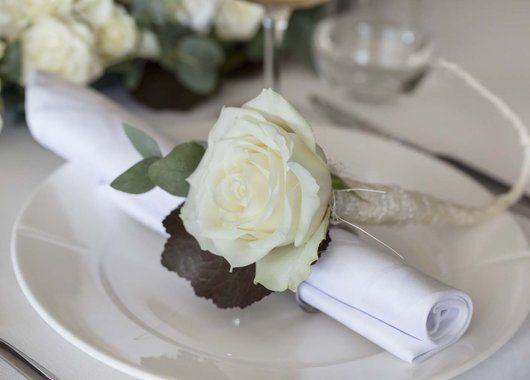 En enkel hvit rose er lekker som kuvertpynt.