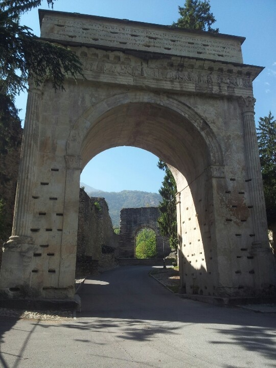 Arco di Augusto, 9 a.C Susa (To) Italia (sullo sfondo i resti dell'acquedotto romano) - - - - - - - - - - IMP · CAESARI · AVGVSTO · DIVI · F · PONTIFICI · MAXVMO · TRIBVNIC · POTESTATE · XV · IMP · XIII · M · IVLIVS · REGIS · DONNI · F · COTTIVS · PRAEFECTVS · CEIVITATIVM · QVAE · SVBSCRIPTAE · SVNT · SEGOVIORVM · SEGVSINORVM · BELACORVM · CATVRIGVM · MEDVLLORVM · TEBAVIORVM · ADANATIVM · SAVINCATIVM · ECDINIORVM · VEAMINIORVM · VENISAMORVM · IEMERIORUM · VESVBIANIORVM · QVADIATIVM · ET ·…