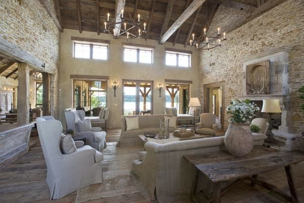 A Rustic Upscale French Barn House on Possum Kingdom Lake in Texas.  - Magnificent Living Room with historic European materials. Crates of 17th century rubble were used for the walls. The floors are from a French stable. The 18th-century limestone mantel in the living room once graced a French farmhouse. The massive front door is easily 300 years old, and it, too, came from a French country house.   Photos by Ross Hailey