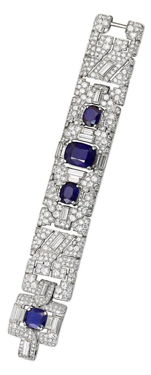 Cartier - A magnificent and extremely rare Art Deco bracelet, 1920s. Designed with a broad geometric design centring upon a large natural, no heat cushion shape sapphire accented by baguettes and old-mine diamonds extending towards two small oval shape sapphires with straight and angular baguettes flowing towards a cushion shape sapphire clasp accented with diamond baguettes; platinum, signed Cartier.