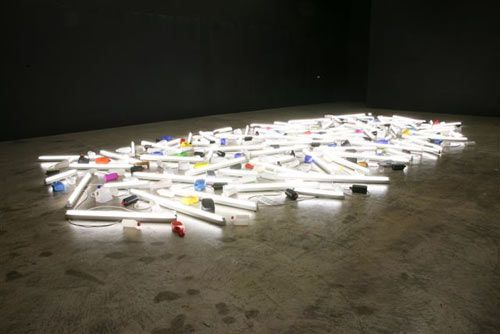 Bill Culbert incorporates lighting and fluorescent tubes along with found objects like lampshades, plastic bottles, and suitcases and brings the viewer's attention to the light and shadows that they create.