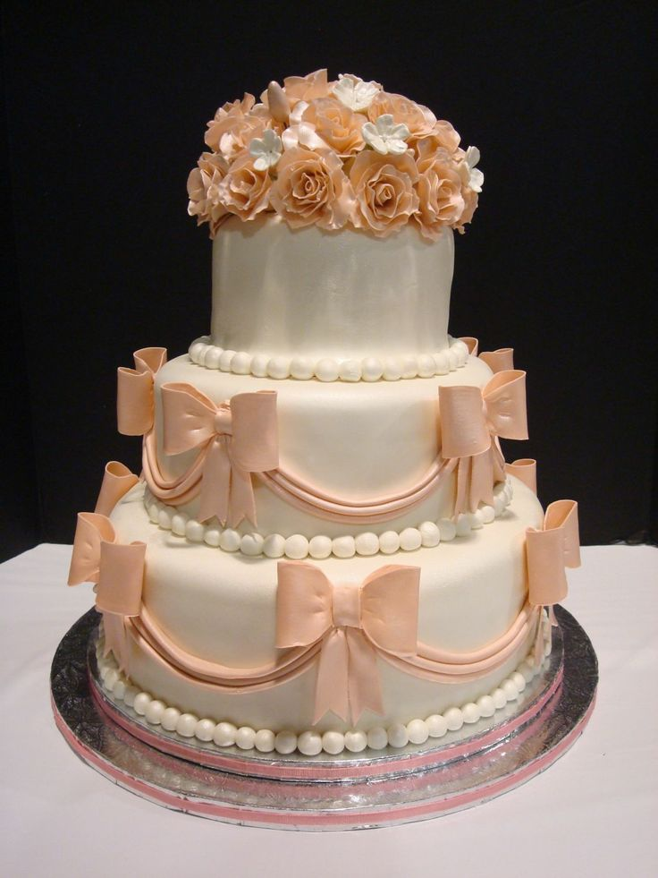"Wedding Cake with Pink Roses & Bows - 6"", 9"", and 12"" round cakes, covered with fondant and decorated with pink roses, bows, and swags."