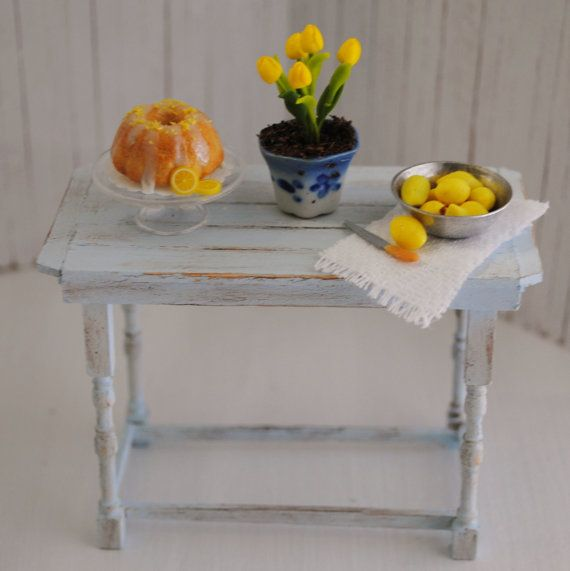 Miniature Light Blue Shabby Chic Kitchen Island With A Lemon Bundt Cake, A Bowl of Lemons, And Yellow Tulips
