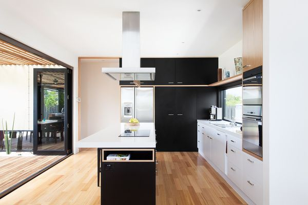 In the kitchen, an island countertop serves as a mixed-use area for cooking, storage, and seating for up to five people. The room opens up to an outdoor dining area. Courtesy of: Archiblox