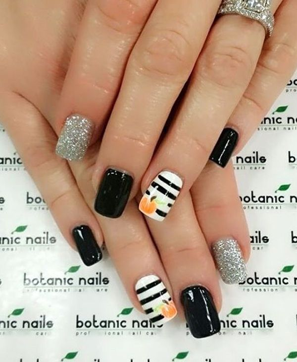 Add a touch of glamour into your spooky nails with this black and white themed pumpkin nail art design. Use black and white as your base colors and paint on pumpkin details on your nails. You can also finish off with silver glitter paint.