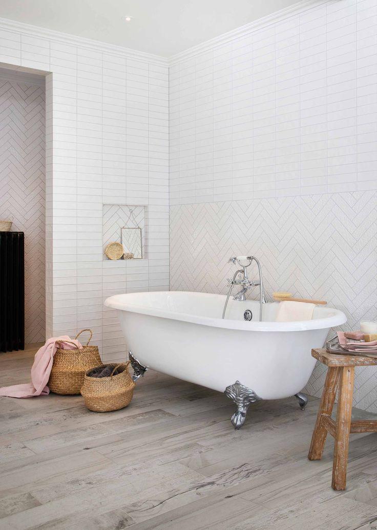 Een vrijstaand bad met pootjes op een stoere houtlook tegel op de vloer is niet van echt hout te onderscheiden