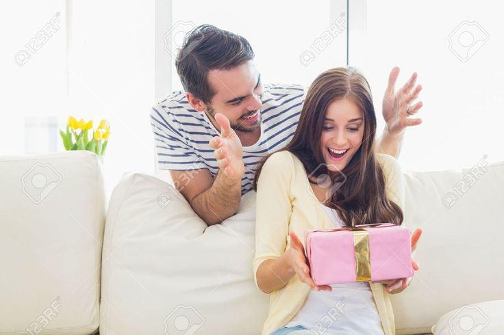 Man surprising his girlfriend with a gift on the couch at home in the living room Stock Photo , #AD, #gift, #couch, #girlfriend, #Man,