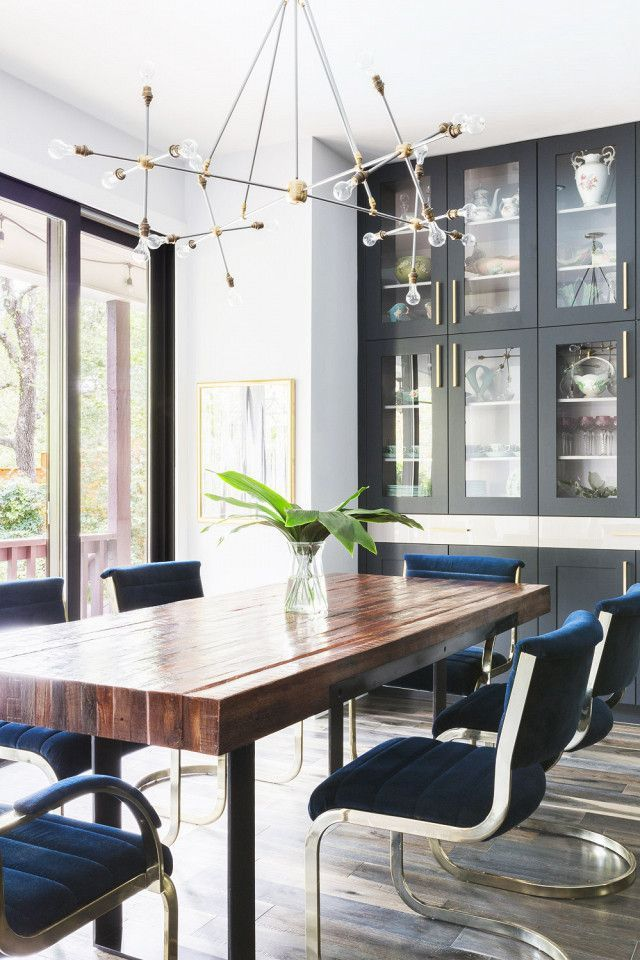 Dining room nook with with a modern chandelier, a gray china cabinent, a reclaimed wood table, and blue velvet chairs