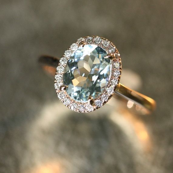 This elegant and feminine Aquamarine ring features a 9x7mm oval shaped natural Aquamarine surrounded by sparkling conflict free natural diamonds set