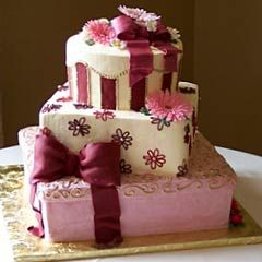 This three tier pink, white and burgundy gift box wedding cake has one round tier and two square cakes positioned on an angle. Decorated with burgundy fondant ribbon and pink marigolds. From Manassas Cakery ........ #wedding #cake #birthday