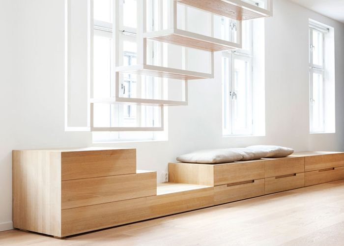 A split level apartment in Oslo, with an amazing steel staircase. As the steps ends before reaching the floors, you have to step down over a piece of wooden furniture that functions both as a chest of drawers and a window seat. We love the idea behind those pieces which makes