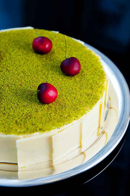 Cheesecake Mosaïc - Made with a sweet pastry dough, topped with a pistachio cheesecake layer, covered with a pistachio-cream cheese mousse, decorated with shards of salted white chocolate around the edge and a dusting of pistachio powder, and topped with sour cherries poached in a vanilla syrup.